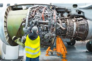 Aircraft mechanic repairing jet engine
